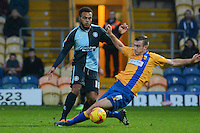 Wycombe Wanderers Aaron Amadi-Holloway just avoids the sliding challenge from Mansfield Town's Lee Collins during the Sky Bet League 2 match between Mansfield Town and Wycombe Wanderers at the One Call Stadium, Mansfield, England on 31 October 2015. Photo by Garry Griffiths.