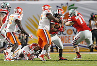 Ohio State Buckeyes running back Carlos Hyde (34) gets tackled Clemson Tigers defensive end Tavaris Barnes (9) in the 2nd quarter of their game against Clemson Tigers in the Discover Orange Bowl at Sun Life Stadium in Miami Gardens, Florida on January 3, 2014.(Dispatch photo by Kyle Robertson)