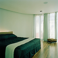 The master bedroom is minimally furnished and has a cool, calm ambience.
