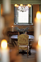 A view of the toile de Jouy chairs in the dining room  through lit candles