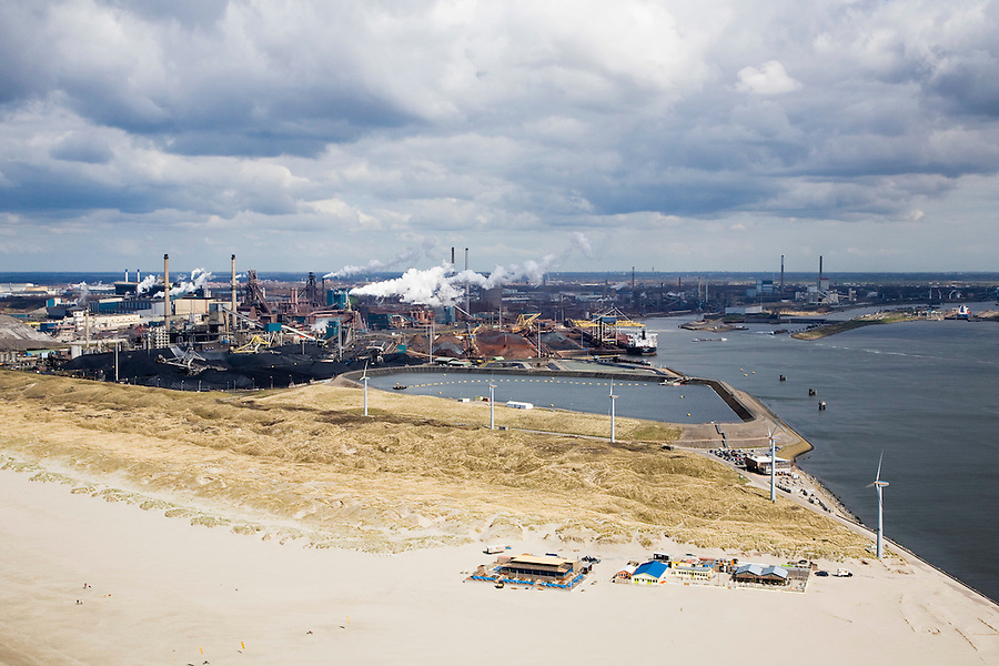 Nederland, Noord-Holland, Velsen, 16-04-2008; strand bij Velsen met strandtent; achter de duinen het depot voor (zout en vervuld) baggerslib; in de achtergrond het terrein van Corus en achter het depot de buitenhaven met de opslag voor erts, kolen, cokes; het complex ligt in Velsen-Noord, naast de sluizen van het Noordzee kanaal (tegenover IJmuiden); Corus: voorheen Hoogovens gefuseerd met British Steel; slibdepot, bagger, slib, baggeren..luchtfoto (toeslag); aerial photo (additional fee required); .foto Siebe Swart / photo Siebe Swart