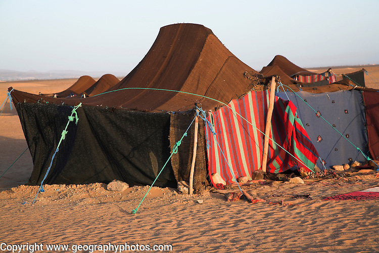 Nomadic Berber tents used as overnight camp by tourist groups camel trekking, Sahara desert, near Zagora, Morocco, north Africa