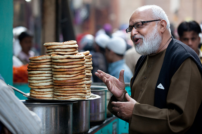 03/02/11 NEW DELHI, INDIA. Pushpesh Pant, Indian academic and author of a definitive book on Indian cuisine ' India Cookbook '.   Here he is seen wandering the streets of Delhi's Sufi Muslim quarter, Nizamuddin, sampling some of the traditional fare on offer such as biryani, kebabs and many types of different breads that are a staple of Indian food. Picture by Graham Crouch/The Australian
