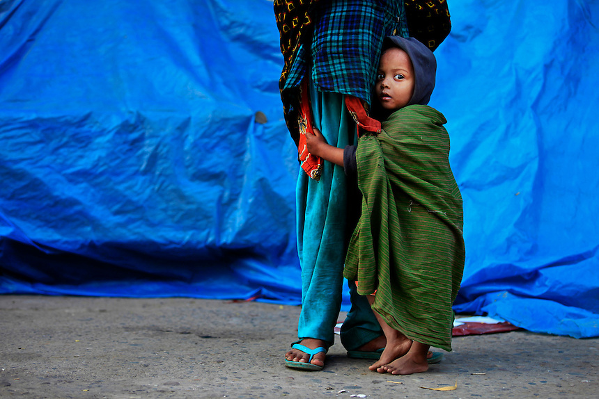 A Bangladeshi child holds his mother, who awaits work with other daily wage laborers by the side of a road in Dhaka, Bangladesh.