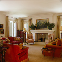The drawing room is furnished with red velvet sofas and a pair of wing-backed armchairs