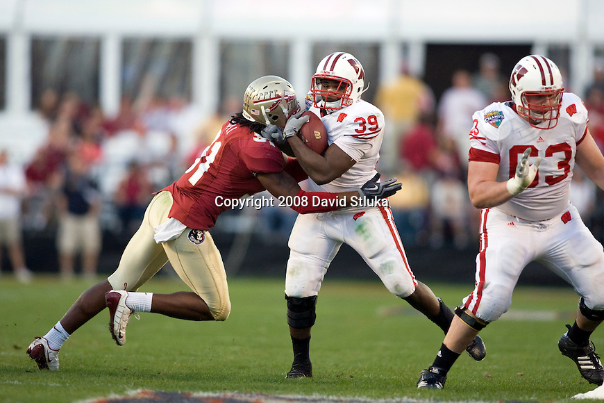 ORLANDO, FL - DECEMBER 27: Linebacker Toddrick Verdell #31 of the Florida State Seminoles tackles running back P.J. Hill #39 of the Wisconsin Badgers during the Champs Sports Bowl on December 27, 2008 at the Citrus Bowl in Orlando, Florida. Florido State beat Wisconsin 42-13. (Photo by David Stluka)