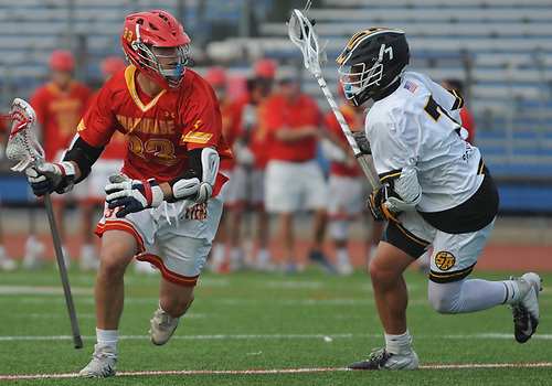Will Kusnierek #33 of Chaminade, left, gets pressured by Andrew McAdorey #7 of St. Anthony's during the Nassau-Suffolk CHSAA varsity boys lacrosse Class AA final at Mitchel Athletic Complex on Tuesday, May 15, 2018. The game went to halftme tied 8-8 when a prolonged lightning storm forced a postponement.