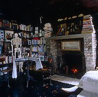 A skeleton stands next to the small dining table in the library corner of the living room which has a blackened wood floor