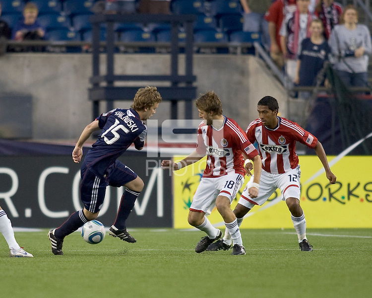 New England Revolution forward Zack Schilawski (15) attempts to control the ball as Chivas USA midfielder Blair Gavin (18) and Chivas USA defender Dario Delgado (12) stand ready. Chivas USA defeated the New England Revolution, 4-0, at Gillette Stadium on May 5, 2010.