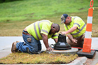 NWA Democrat-Gazette/J.T. WAMPLER Greg Battles of Rogers (left) and Shawn Herron of Tontitown work Thursday April 20, 2017 at installing a pedestrian crossing signal at the Central Ave. intersection with the Razorback Greenway Trail in downtown Bentonville. Battles and Herron work for All Electric Service.