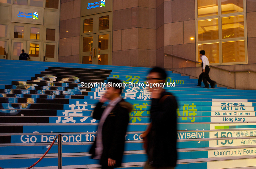 A couple of men pass the Standard Chartered Bank  in Hong Kong..