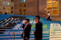 A couple of men pass the Standard Chartered Bank  in Hong Kong..