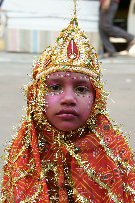 child sitting in the strees of holy city Pushkar dressed up as a god  waits for donations,  Rajastan, India
