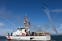 """The USCG cutter """"Hawksbill"""" (WPB-87312) patrols San Francisco Bay as the Blue Angels do a formation break above."""