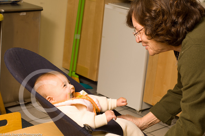 Day Care Center infant room female caregiver interacting with baby
