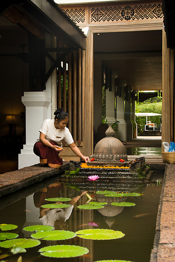 A woman puts the finishing touches on the intricately placed flowers at the La Residence Phou Vao Hotel in Luang Prabang, Laos.