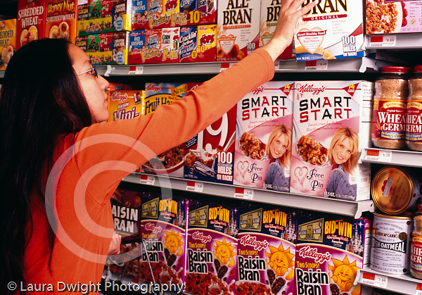 College student female shopping at supermaket, reaching for box in cereal section