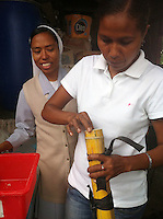 February 22nd, 2013_ Baucau, TIMOR-LESTE_ Ai-Funan soap team coordinator Mariquita Fatima da Costa (right) test a method of using bamboo to create round soaps while being observed by a Canossian nun  in Baucau, Timor-Leste.  The Conassian sisters have help support the Ai-Funan woman's soap cooperative.  Photographer: Daniel J. Groshong/The Hummingfish Foundation
