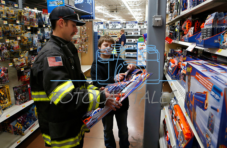 Clay Peterson, with Carson City Fire, shops with Charles, 13, at the 15th annual Holiday with a Hero program at Walmart in Carson City, on Wednesday, Dec. 19, 2018. The program, which pairs local heroes with more than 200 K-8th graders, provides a $100 Christmas shopping spree at Walmart.  <br /> Photo by Cathleen Allison/Nevada Momentum
