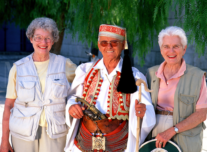 A senior, smiling Greek man in traditional attire poses with two female tourists. Greece.