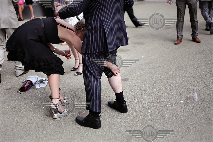 A woman bends down to adjust the leg of a man's suit at the Royal Ascot race meeting. The annual event, during which each day begins with the Queen's arrival in a horse drawn carriage, dates back to 1711 when Queen Anne organised the first races on what was then a heath near Windsor Castle.