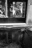 Milano, asfaltatura di un marciapiede in via Savona. Una bambina osserva dalla vetrina di un negozio --- Milan, asphalting a sidewalk in Savona street. A little girl looks out of the window of a shop