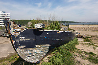 old wooden fishing boat on shore, by the sea in Denmark, Scandinavia, used for growing plants in front of a new housing complex by the sea shore in Aarhus Denmark