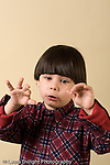 preschool boy singing and making hand gestures vertical closeup