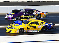 Nov 10, 2013; Pomona, CA, USA; NHRA pro stock driver Jeg Coughlin Jr (near lane) races alongside Vincent Nobile during the Auto Club Finals at Auto Club Raceway at Pomona. Mandatory Credit: Mark J. Rebilas-