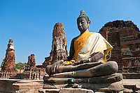 A sitting Buddha surrounded by the ruins of Wat Mahathat in Ayutthaya. Ayutthaya was the ancient capital of the southern Kingdom of Siam from 1350 until it was sacked by the Burmese in 1767. in 1976, the site was declared a historical park and renovation work began to reveal the glory of the original city. The park was declared a UNESCO World heritage site in 1991.