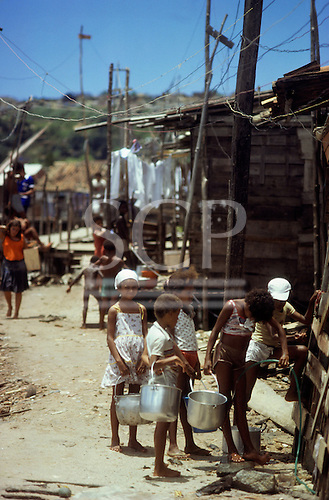Salvador, Brazil. Favela children queueing to collect water from the communal tap; Alagardos favela,  Bahia State.