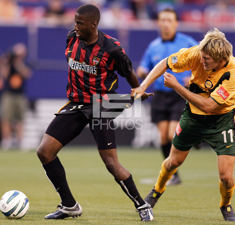 The Galaxy's Sasha Victorine fouls the MetroStars' Cornell Glen under the watchful eye of referee Alex Prus. The NY/NJ MetroStars defeated the LA Galaxy 3 to 0 during MLS action at Giant's Stadium, East Rutherford, NJ, on August 8, 2004.