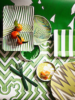 Still life of a table with plates overlapping and a knife and fork, taken from above. All the crockery and cutlery have geometric patterns. The whole image is dominated by green patterns. Oranges and smoked salmon bring in an orange colour to the image. Styling by Victoria Tunstall.