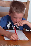 5 year old boy at home writing letters vertical
