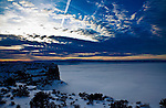 Mist fills the deep canyon during a winter sunset at Canyonlands National Park, Island in the Sky section, near Moab, Utah.