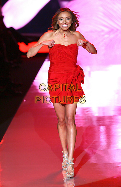 GIULIANA RANCIC.The Heart Truth Fall 2011 fashion show during Mercedes-Benz Fashion Week at The Theatre at Lincoln Center on New York City, New York, NY, USA,.9th February 2011..catwalk runway model modeling full length red dress hands strapless ruched mini walking smiling strappy sandals beige .CAP/ADM/PZ.©Paul Zimmerman/AdMedia/Capital Pictures.