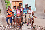 St. Julia Josophot and her husband Labonte Petithomme sit with their children on the porch of their new home in Lareserve, a village near Jean-Rabel in northwestern Haiti. The family's previous house was destroyed during Hurricane Matthew in 2016, and Church World Service, a member of the ACT Alliance, helped the family build their sturdy new home.