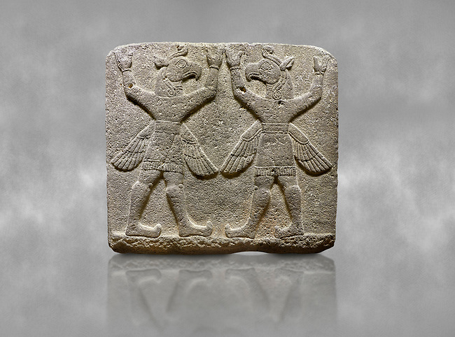 """Hittite relief sculpted orthostat stone panel of Herald's Wall Basalt, Karkamıs, (Kargamıs), Carchemish (Karkemish), 900-700 B.C. Bird-headed, winged figures of human body. Anatolian Civilisations Museum, Ankara, Turkey.<br /> <br /> These figures are called as """"Winged Griffin Demons"""". Embossing is constructed symmetrically. Their hands are on their heads. It is assumed that they carry the heavens. <br /> <br /> Against a grey art background."""