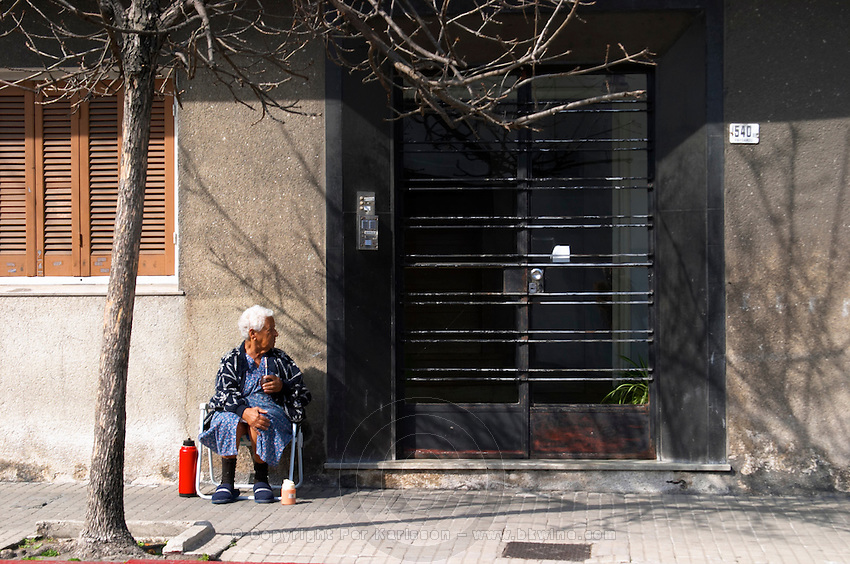 An old woman sitting on the pavement drinking mate herbal tea, with a red thermos warm water flask in front of a black iron gate door. Montevideo, Uruguay, South America