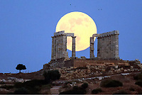 A full moon rising over the ruins of the Temple of Poseidon in Sounio, Greece. Friday 09 June 2017