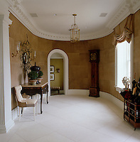 Mellow ochre walls give a welcoming warmth to the elegant and imposing entrance hall