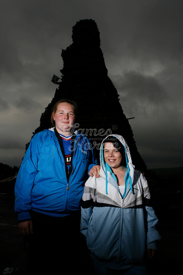 Teenage girls Stacey and Laura stand infront of the 30 meter tower of pallets and old tires that will become a giant bonfire to burn the Irish flag on the Loyalist estate of New Mossley, Belfast Northern Ireland.The bonfires which are seen by the Protestant community as a celebration of loyalist culture in the province are lit on the eve of 12 July, which is the anniversary of the Battle of the Boyne at which the Protestant King William of Orange defeated the Catholic King James in 1690. The festival causes outrage in the nearby republician and Catholic areas of the city.