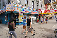 A bodega next to a Kennedy Fried Chicken in the neighborhood of Harlem in New York on Sunday, August 9, 2015. (© Richard B. Levine)