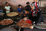 Palestinians wait as they cook their foods in a traditional mud oven during the holy fasting month of Ramadan, in Rafah in the southern Gaza Strip on June 19, 2016. Ramadan is sacred to Muslims because it is during that month that tradition says the Koran was revealed to the Prophet Mohammed. The fast is one of the five main religious obligations under Islam. More than 1.5 billion Muslims around the world will mark the month, during which believers abstain from eating, drinking, smoking and having sex from dawn until sunset. Photo by Abed Rahim Khatib