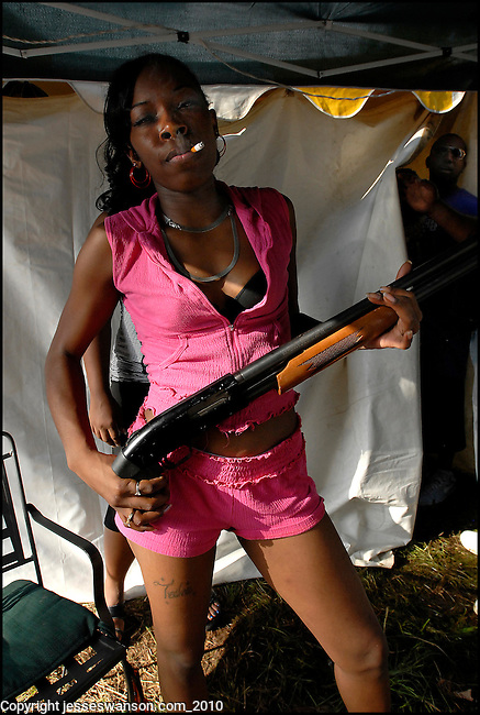 Tesha, an exotic dancer at the Footwash in Greir, Hale County, holds a shotgun in front of The Pussy Tent, where patrons pay to see women strip dance. The Footwash began as a religious festival and has taken place outdoors on a 600-acre farm every year since 1888, making it one of the longest running festivals in the country and drawing crowds estimated at more than 20,000 over a weekend.