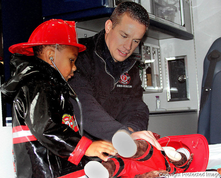 Devon Degiacomo (age4) learns how to work in an ambulance from Holbrook Fireman David Burke during the Holbrook Fire Department open house on Saturday, Oct. 11, 2014.<br /> (Photo by Gary Wilcox)