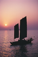 A traditional fishing junk sails across Lake Tai in the red light of sunset. Lake Tai is China's third largest fresh water lake and links with the Grand Canal.