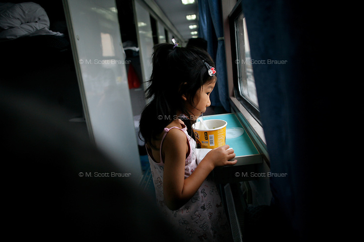 A girl eats ramen noodles on a train between Hong Kong and Shanghai, China.