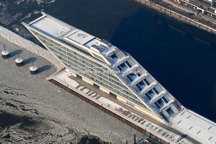"""4415/Dockland: EUROPA, DEUTSCHLAND, HAMBURG  28.01.2006 Dockland.  Der Name ist in Anlehnung an die schick restaurierten Hafenanlagen in London gewaehhlt. Und wie immer, wenn Star-Architekt Hadi Teherani Hand anlegt, ist eine eigenwillige, aufregende Form garantiert. Das 25 Meter hohe """"Dockland"""" ist ein 30 Mio Euro teurer Buero-Glaspalast in Form eines Schiffes, das mitten in der Elbe steht. Dafür musste am ehemaligen Englandfaehren-Terminal extra eine kleine Insel aufgeschuettet werden..Das """"Schiff"""" ragt sechs Geschosse hoch ueber die Elbe, die Bueros im Bug ueberschatten den Fluss 40 Meter weit. Einen aufregenderen Ausblick vom Schreibtisch gibt's nicht...Das Haus, dessen Stahlskelett auf einer Werft gefertigt und per Ponton zum Bauplatz verschifft wird, verspricht, ein besonderer Blickpunkt am Hafenrand zu werden. ."""