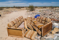 discarded couch sits in sun as desert of Northern Baja California serves as trash dump for nearby residents, South of San Felipe, Baja California, Mexico